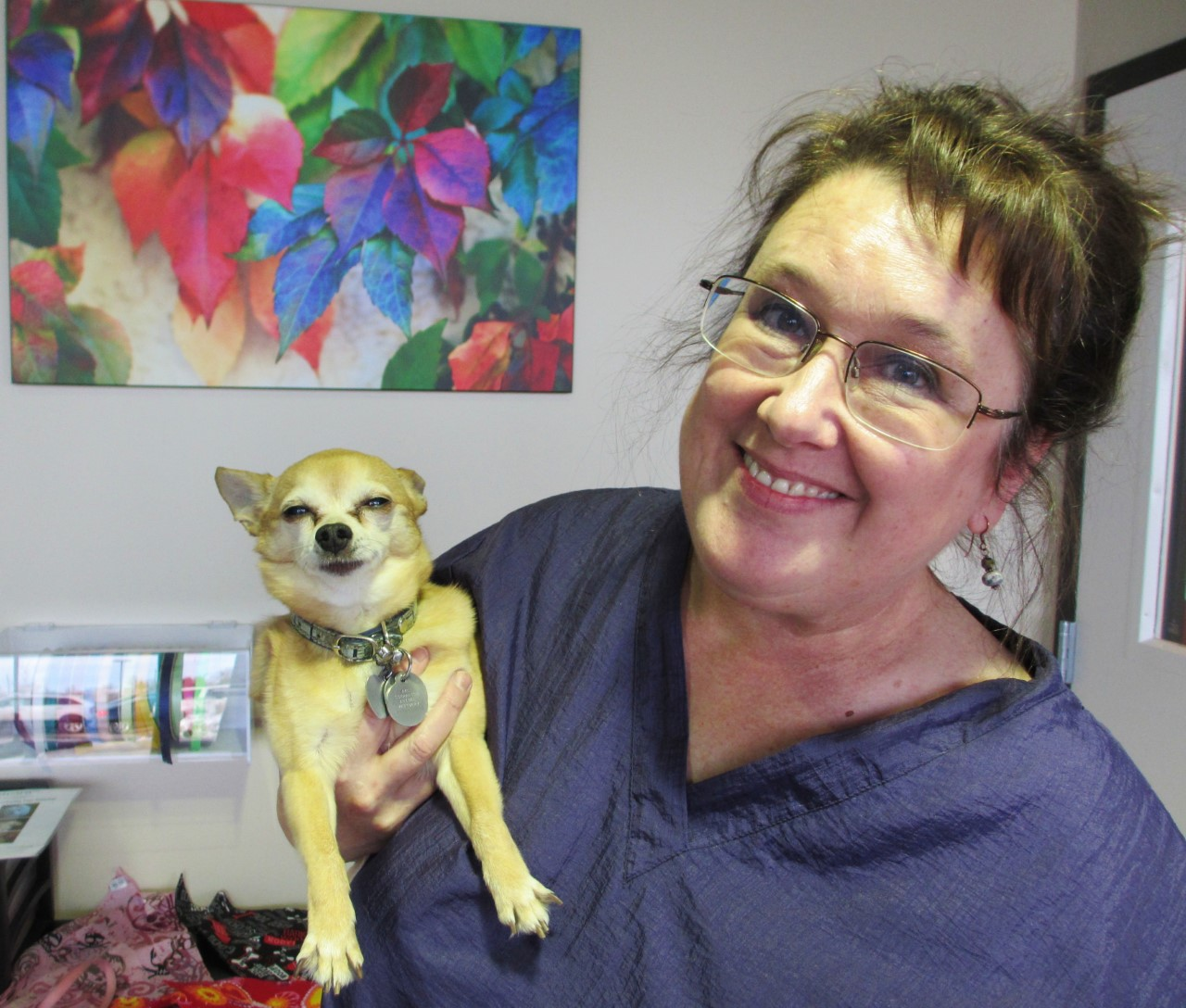 Woman with glasses holds small dog